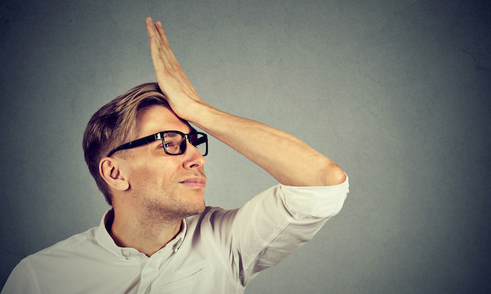 Regrets wrong doing. Silly young man, slapping hand on head having a duh moment isolated on gray background. Negative human emotion facial expression feeling, body language, reaction
