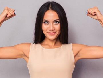 Happy elegant woman showing her biceps