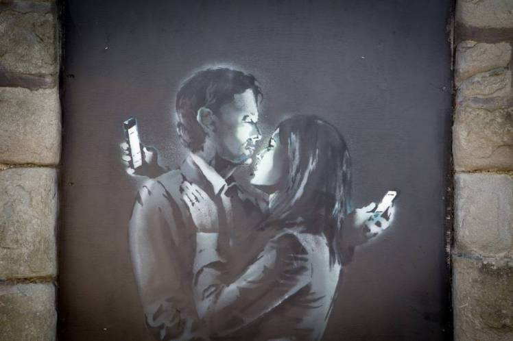 "A new Banksy artwork which has appeared on a doorway in Bristol city centre in the last  couple of days. The piece was confirmed on his website. 15 April 2014.  The ""mystery"" location of new street art by ""guerrilla artist"" Banksy has been tracked down to a Bristol street. See swns story SWBANKSY. The artwork, showing a couple embracing while checking their mobile phones, was posted on Banky's website on Monday - but its whereabouts were kept a secret . The location has now been identified as Clement Street in the city. It comes after Cheltenham Borough Council said it would be happy to help protect another piece of art, believed to be by Banksy, on a wall in the town. The artwork, depicting three men using listening devices to ""snoop"" on a telephone box, appeared on Sunday on the side of a house in Fairview Road, Cheltenham."